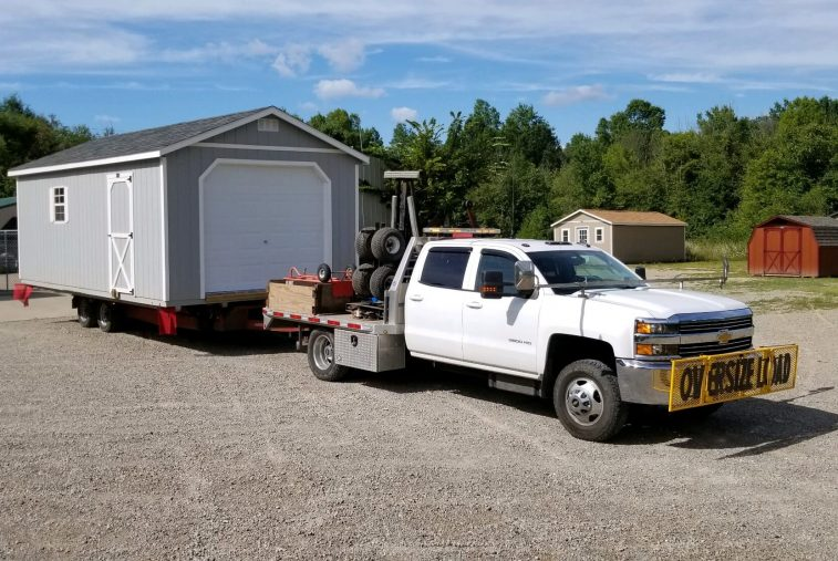 Yoder Building Company delivery truck with a shed on the trailer